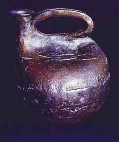 Hand built stoneware jug that looks like a primitive Scottish curling stone.